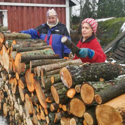Ritva ja Jouko Mild pinoavat polttopuuta kotona Naantalissa.