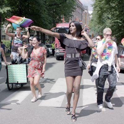 Kelet går mitt i ett Pridetåg i Helsingfors och håller i prideflaggan.