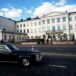 Suomenlipulla varustettu auto presidentinlinnan edustalla