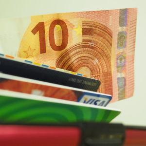 En tioeurossedel kommer fram ur en plånbok. Ett busskort och bankkort syns också delvis.