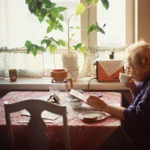 Äldre dam sitter i köket och dricker kaffe