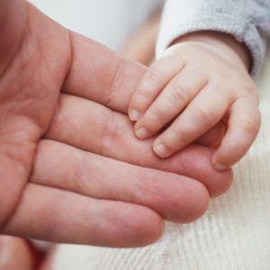 En vuxens hand och en barnhand