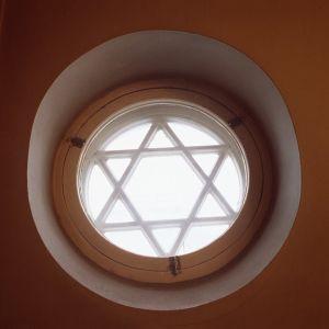 Pyöreä ikkuna, jossa Daavidin tähti. Helsingin juutalainen seurakunta.