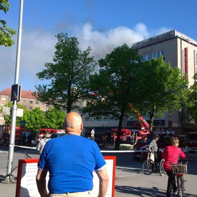 Rakennuksen katolta nousee savua.