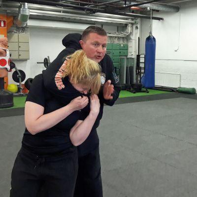 Mies ja nainen harjoittelevat itsepuolustuksen otteita.