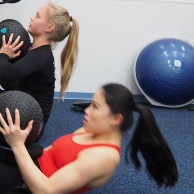 Kaksi taitoluistelijaa tekee vatsalihaksia painopallojen kanssa.