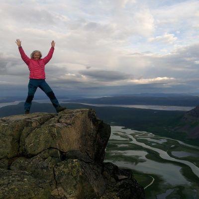 kika fogelberg sträcker upp händerna i luften på toppen av ett berg under kungsledenvandringen