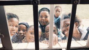 Nyfikna barn utanför ett fönster.