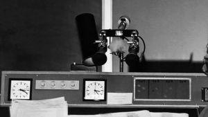 Radiokuuluttaja Kaisu Puuska-Joki istuu studion tuolilla ja hymyilee kameralle vuonna 1960