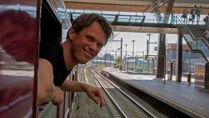 Tågresenär hänger ut genom ett fönster då tåget står på en perrong.