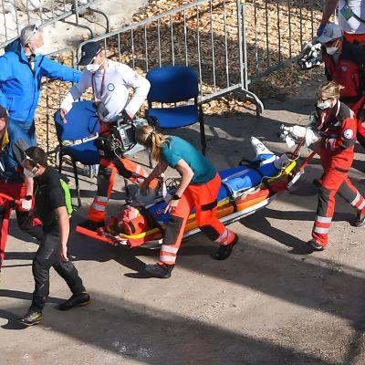 Daniel-André Tande transporteras bort från backen i en pulka av vårdpersonal.