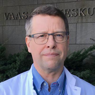 Man med läkarrock står framför Vasa centralsjukhus. Ser allvarlig ut.