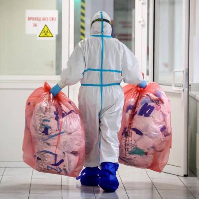 En person med skyddsutrustning bär två stora plastpåsar med avfall i händerna. Personen går mot en dörr i en sjukhuskorridor.