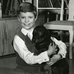 Svartvit bild av Kung Carl XVI Gustaf som barn, i famnen håller han en hund.