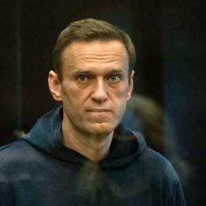 Aleksei Navalnyj i mörkblå munktröja i sin cell där han står och bevakas av en vakt.