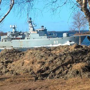Ett militärfartyg som kör väldigt nära land på Åland.