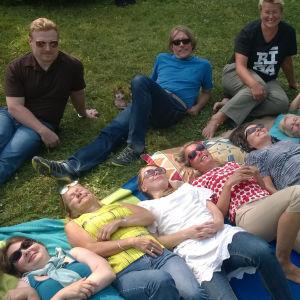 Kesäisellä ruohikolla makaa 9 naista iloisesti hymyilleen. Taka-alalla istuu kolme henkilöä
