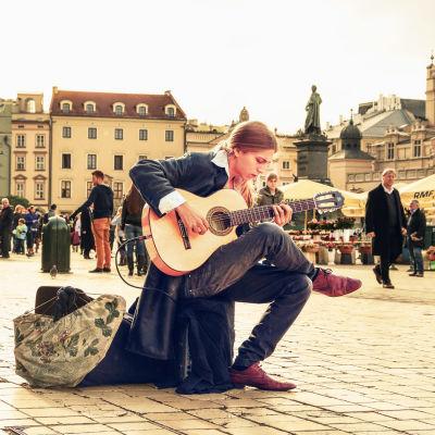 Kitaraa soittava henkilö toriaukion keskellä