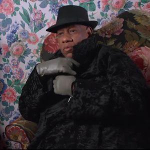 Muotitoimittaja André Leon Talley istuu mustassa turkisviitassa kukikkaan tapetin peittämän seinän edessä. Kuva dokumenttielokuvasta.