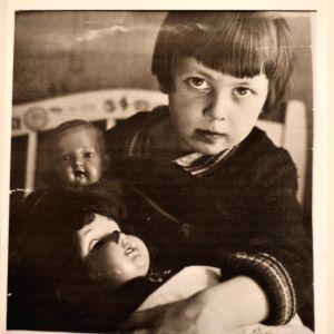 En gammal bild av en flicka som har två dockor i famnen.