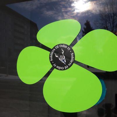 Keskustapuolueen logo, jonka keskelle on liimattu Soldiers of Odin -järjestön tarra.