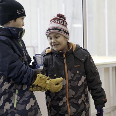 Kaksi poikaa jääkiekkokaukalon reunalla.