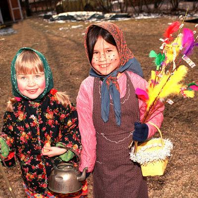 Kaksi iloista tyttöä pääsiäisnoitina virpomassa.