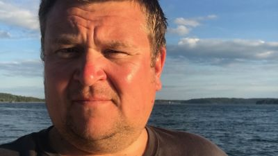 Närbild på en medelålders man. I bakgrunden syns havet.