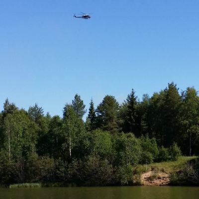 En helikopter flyger över olycksplatsen