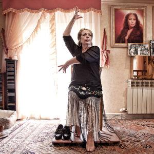 La Chana dansar flamenco sittandes i sitt vardagsrum.