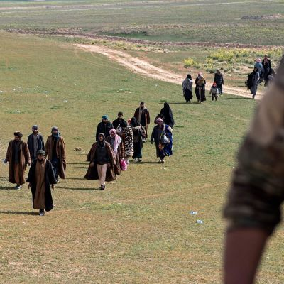 Isis-taistelijoiksi uskotut miehet ja heidän perheenjäsenensä poistuvat peltojen yli.