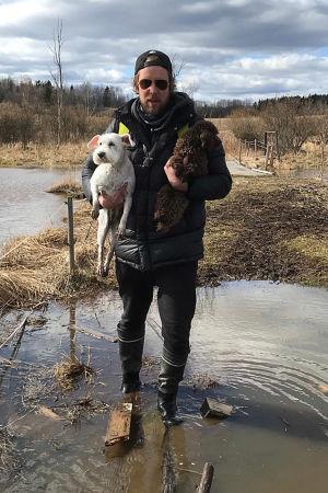 Oopperalaulaja Waltteri Torikka suomaisemassa lemmikkikoirat kainalossa.