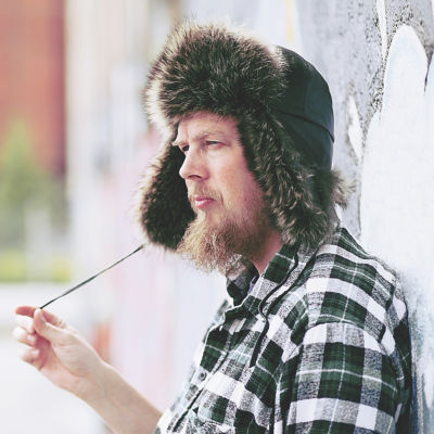 Tuomas Kyrö nojaa kiviseinään karvalakki päässänsä.