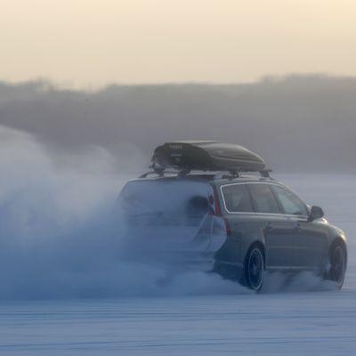 auto ajaa jäällä ja lumi pöllyää