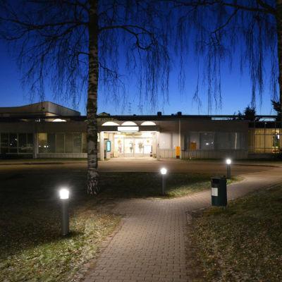 På bilden syns ingången till Borgå sjukhus om kvällen. Dörrarna finns på mitten av det avlånga huset. Den mörkblå kvällshimlen och några björkkvistar som hänger ner synns uppe på bilden.