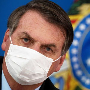 Brasiliens president Jair Bolsonaro med ansiktsskydd på sig. Brasiliens flagga syns till höger om honom.