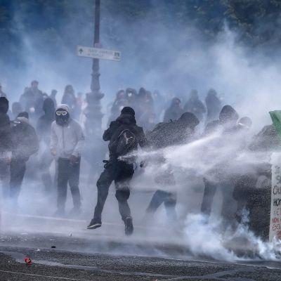 Mielenosoittajat suojautuvat jäteastioiden taakse vesitykkien suihkuilta.