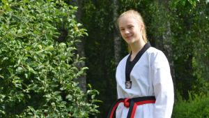 En ung kvinna i taekwondodräkt tittar in i kameran. Hon står utomhus framför ett äppelträd.