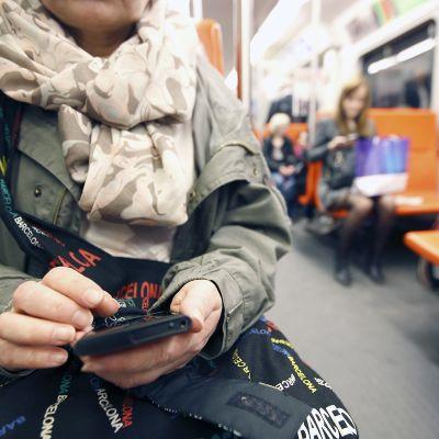Nainen katsoo puhelintaan metrossa