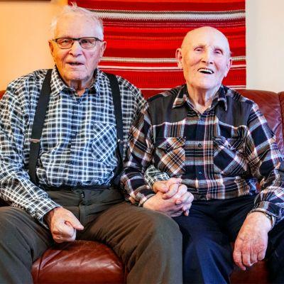 Eino ja Väinö kinnunen istuvat sohvalla ja pitävät käsiä.