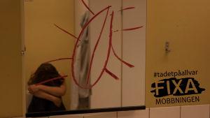 Ledsen flicka vid spegel med klotter