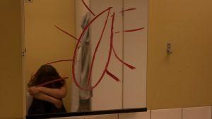 Klotter på en spegel och en olycklig ungdom.