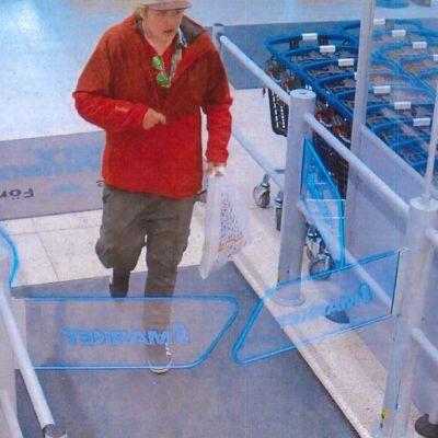 En man i röd blus och skärmmössa som går i en mataffär. Polisens foto på en misstänkt rånare i Karis.