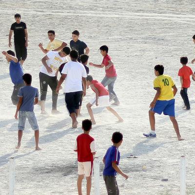 Lapset pelaavat jalkapalloa.