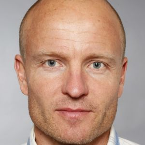 Juha-Pekka Triipponen, en man med skäggstubb och blåvitrutig skjorta.