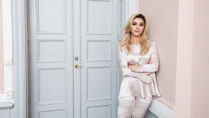 Michaela Forni iklädd en vit blus och vita byxor av siden. Hon står framför en stängd dörr, och lutar sig mot väggen bredvid.