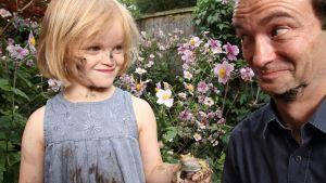 sammakko, lapsi ja mies puutarhassa plk