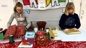 Kaksi tyttöä paketoi lahjoja.