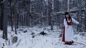 Kansallispukuinen nainen metsässä