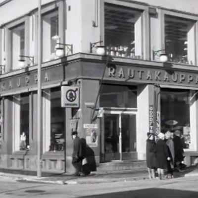 Ihmisiä kadulla rautakaupan edessä (1960-luku)